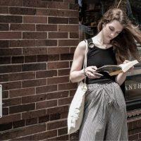 Момиче, четящо книга на улица в Ню Йорк